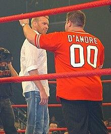 Scott D'Amore (di spalle) mentre parla con Christian Cage.