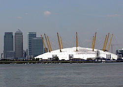 The O2, with the Canary Wharf complex in the background, seen from the River Thames. The London 2012 logo, which has now been removed from the dome, can be seen advertising the fact that it would be an Olympic venue.