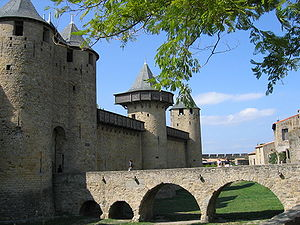 Carcassonne, France, showing the classic features of the enceinte walls, defensive ditch, cylindrical flanking towers, a gatehouse, and wooden defensive structures