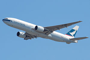 Front quarter view of a Cathay Pacific 777 in flight with flaps and landing gear retracted