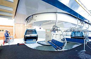 """Hybrid lift - The """"Panorama Bahn"""" hybrid lift in Turracher Höhe, Austria. Chairs load from the station on the left of this image, gondolas along the carpeted area to the right."""