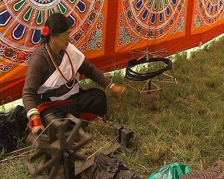 Mujer nepalí usando una rueca llamada pan c