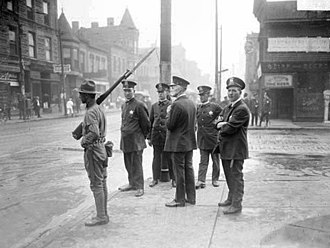 Chicago race riot of 1919 - Five police officers and a soldier with a rifle and bayonet standing on a corner in the Douglas neighborhood.