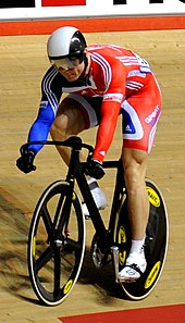 Chris Hoy wearing a bicycle helmet, visor, cycling shorts and top cycling on a racing bike in a velodrome.