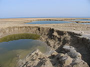 Sinkholes near the Dead Sea, formed by dissolution of underground salt by incoming freshwater, as a result of a continuing sea level drop.