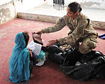 Defense.gov News Photo 111203-F-SA682-046 - U.S. Navy Petty Officer 1st Class Rachael Bradley with the Kandahar Provincial Reconstruction Team hands out winter clothes to a girl during a.jpg