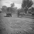 Een auto en een rijtuig (deeleman genoemd) op een geasfalteerde weg met gaten, Bestanddeelnr 255-6712.jpg
