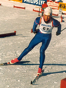 A man skies on a snow-covered course. He is wearing a white vest on top of a blue skin-tight jumpsuit, a white winter cap, and red ski boots. On his back, he carries a rifle.