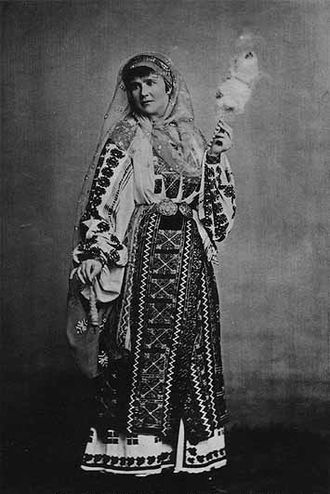 Textiles in mythology and folklore - A royal portrait employing strong mythic overtones: Queen Elisabeth of Romania, born a German princess, adopts the national costume of Romania, with distaff and spindle.