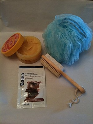 Exfoliation (cosmetology) - Exfoliation methods used in Canada in 2011.  Shown: top right, a bath sponge made of plastic mesh; lower right, a brush with a pumice stone on one side and a natural bristle brush on the other side, for foot exfoliation; lower left, a mud mask package for facial exfoliation; top left, a jar of perfumed body scrub to be used while bathing.