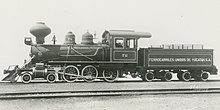 A black-and-white image of an old steam locomotive and tender