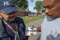 FEMA - 30687 - Resident shows a FEMA worker a photograph of the flood.jpg