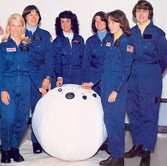 Judith Resnik - One of the first six women NASA astronauts, Resnik (third from left) stands behind a prototype Personal Rescue Enclosure