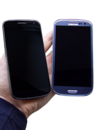 Photo of two phones turned off held next to each other with warm yellow ambience lightning. The phones are rested on a person's hand.