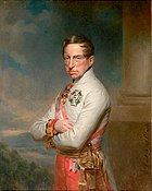 Half-length oil portrait of the Archduke Charles. He wears a white high-collared military jacket of the Austrian army and has a red and white sash over his right shoulder. He wears two decorations, a cross on his breast and another medal at his neck. Charles has a long fleshy face, short brown hair and light eyes. He gazes calmly towards the viewer. His arms are folded across his chest.