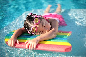 A young girl taking a break in a swimming pool...