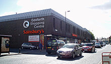 A 1970s monolithic shopping centre, mostly grey/brown in colour. In the foreground the busy high street with a number of travelling cars.