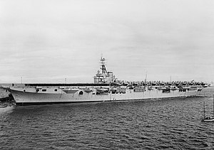 An aircraft carrier travelling at slow speed. Naval personnel in black uniforms are lined up on the forward half of the flight deck, while propeller aircraft with folded wings crowd the back half.