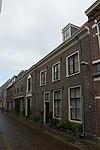 foto van Koetshuis en stallen van het er achter gelegen erf aan de Nieuwe Gracht, houtversierde middenpartij, grote staldeuren