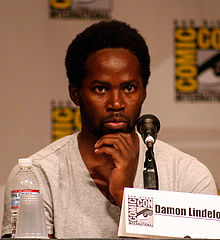 "A black man wearing a white shirt. A panel with the logo for the San Diego Comic-Con is seen behind him. In front of him are a water bottle, a plastic cup, a microphone and a paper reading ""Damon Lindelof""."
