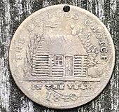 "A worn, holed brass token with a log cabin and cider keg on it and reading ""The people's choice in the year 1840"""