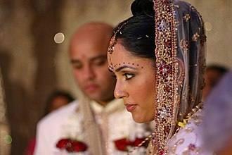 Bindi (decoration) - Bride with decorative bindis and maang tikka between hair parting where married women apply sindoor.