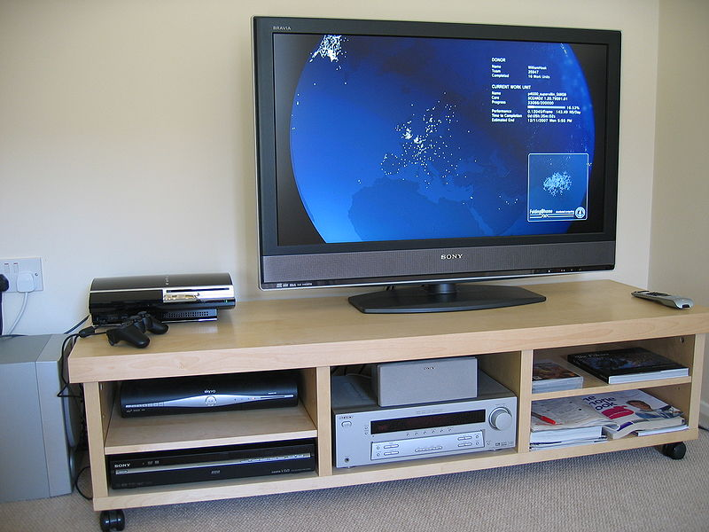 A television screen with various media devices underneath
