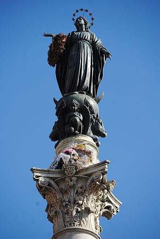 Column of the Immaculate Conception, Rome - The Blessed Virgin Mary as the Immaculate Conception carrying a wreath of flowers offered annually by the Roman firemen.  Sculpture by Giuseppe Obici on top of the Corinthian column of the goddess Minerva.