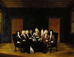 A painting showing eight bewigged men, sat around a table with papers and quills
