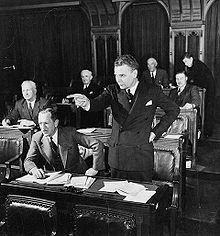 Diefenbaker, der in einer gesetzgebenden Kammer steht, zeigt dramatisch vor sich hin.  Sein Haar ist ergraut, und er sieht ganz so aus, wie er es als Premierminister tun wird.