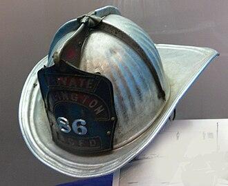 Firefighter's helmet - A traditional metal firefighting helmet from Arlington County, Virginia, c. 1974