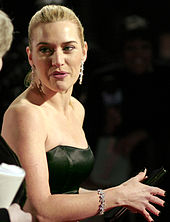 A young woman in formal evening attire of a strapless black gown, with diamond earrings and bracelet, looks over her shoulder. Her hair is pulled back from her face, and her hand, with dark nail varnish clasps a purse.