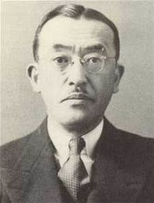 Close up of the head and shoulders of a solemn middle-aged Japanese man with a small mustache. He is wearing a suit, tie, and glasses.