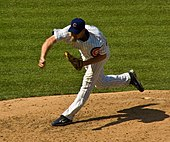 "A man sporting a goatee and wearing a dark blue baseball cap with ""C"" in the middle, a pinstriped jersey and black Nike cleats delivers a pitch."