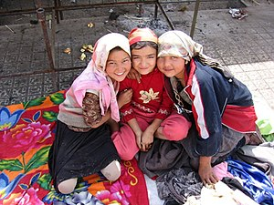Three Uyghur girls at a Sunday market in the o...