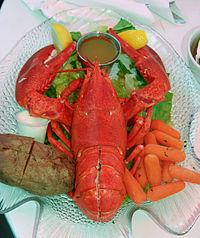 Présentation classique du homard à la nord-amériacaine: les pinces et la queue fendus avec du beurre fondu.