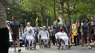 2012 Summer Paralympics - A group of torchbearers in wheelchairs bringing the Paralympic flame through Canary Wharf.