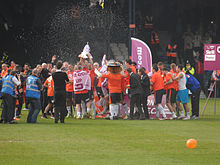 A crowd of men, some wearing grey suits and some wearing white shirts, navy shorts and white socks, celebrate raucously on a podium. An open bottle of champagne is visible in front of them, spiralling through the air as if somebody has thrown it.