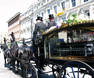 Funeral director - Funeral directors driving a hearse in a funeral procession