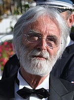 Headshot of a bearded, grey-haired man with glasses. He is wearing a tuxedo and a black bowtie.