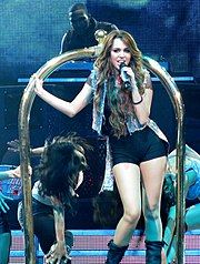 A female teen wearing a torn shirt, shorts, boots and a jean jacket, rides on a luggage cart. Beside her, four back-up dancers bend to the side while dancing