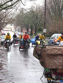 Cyclists pull covered trailers in the rain