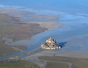Environmental impact of wind power - The surroundings of Mont Saint-Michel at low tide. While windy coasts are good locations for wind farms, aesthetic considerations may preclude such developments in order to preserve historic views of cultural sites.