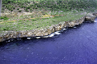 Navassa Island - An aerial photo showing the steep rocky coast that rings the island.