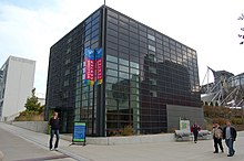 "A cube-shaped building covered by a rectangular grid containing some windows, but mostly black glass. Four people are on the surrounding sidewalks and there are three banners reading ""Welcome Center""."