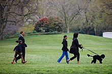 """Michelle Obama and her oldest daughter walk a small black dog whilst Barack Obama and their youngest daughter walk a short distance behind them"""
