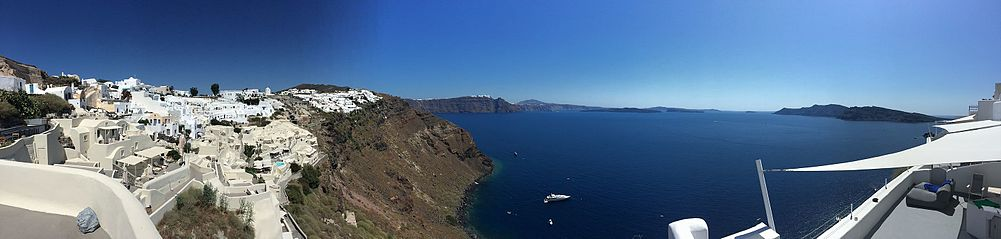 Panoramic view from Oia's cliffs, overlooking the island of Santorini, Thira, Volcano (Palia & Nea Kameni) and beyond.