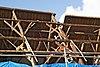 foto van Dwarshuis onder hoog pannen zadeldak tussen puntgevels met rookkanalen in de as. In de voorgevel ankers met jaartal. In de achtergevel ontlastingsbogen
