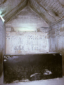 Photograph of Unas' burial chamber. A tall but damaged black sarcophagus stands near the west wall. The walls surrounding the sarcophagus painted to resemble reed mats, and the royal palace façade. The gabled roof is painted with five pointed gold stars. The west gable is inscribed with horizontal lines of hieroglyphs. These spells serve to protect the pharaoh in his sarcophagus.