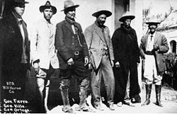 "General Francisco ""Pancho"" Villa with his general staff in 1913. Villa in grey suit in center, Villa's sidekick, General Rodolfo Fierro at far right."